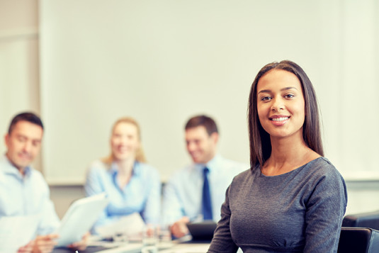 smiling businesswoman with group of businesspeople meeting in office